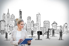Blonde Geschäftsfrau, die Tabletten-PC mit Stadtbild verwendet Lizenzfreie Stockbilder