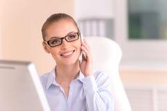 Blonde Geschäftsfrau, die am Telefon im Büro spricht Stockfotografie