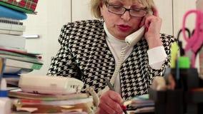 Blonde Geschäftsfrau, die am Telefon, Informationen notierend spricht stock footage