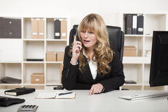 Blonde Geschäftsfrau, die am Telefon spricht Stockfoto