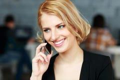 Blonde Geschäftsfrau, die am Telefon spricht Stockfotografie