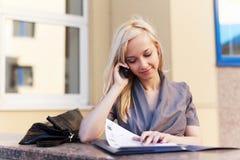 Blonde Geschäftsfrau, die um den Handy ersucht Stockbild