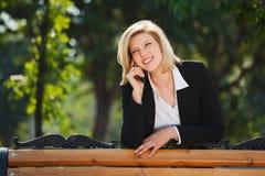 Blonde Geschäftsfrau, die um den Handy ersucht Lizenzfreie Stockfotografie