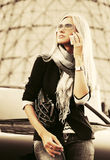 Blonde Geschäftsfrau, die um den Handy ersucht Stockbilder
