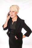 Blonde Geschäftsfrau in einem schwarzen Anzug sprechend an einem Handy Lizenzfreies Stockbild