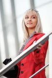 Blonde Geschäftsfrau gegen Bürofenster Lizenzfreies Stockbild