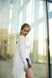 Blonde Geschäftsfrau gegen ein Mallfenster Stockbilder