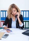 Blonde Geschäftsfrau im Büro an der Telefonschreibensanmerkung Stockfoto