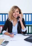 Blonde Geschäftsfrau im Büro am Telefon lachend über Kamera Lizenzfreies Stockbild