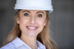 Blonde Geschäftsfrau im Schutzhelm lächelnd an der Kamera Lizenzfreie Stockfotos