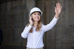 Blonde Geschäftsfrau im Schutzhelm sprechend auf Smartphone und wellenartig bewegender Hand Stockfotografie