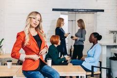 Blonde Geschäftsfrau lächelt an der Kamera mit den Kollegen, die im Hintergrund arbeiten stockbild
