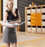 Blonde Geschäftsfrau liest den Klassifikator Stockfotografie