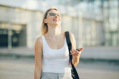Blonde Geschäftsfrau liest eine Mitteilung am Telefon Stockbilder