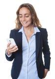 Blonde Geschäftsfrau mit blauen Augen und Blazer, der Mitteilung mit Telefon sendet Lizenzfreie Stockfotos