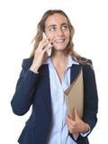 Blonde Geschäftsfrau mit blauen Augen und Blazer, der am Telefon spricht Lizenzfreies Stockbild