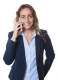 Blonde Geschäftsfrau mit blauen Augen und Blazer, die am Telefon sprechen Lizenzfreie Stockbilder