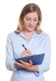 Blonde Geschäftsfrau mit dem Klemmbrettschreiben gemerkt Stockbilder