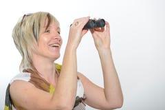 Blonde Geschäftsfrau mit dem Schal, der mit Ferngläsern schaut Stockfotos