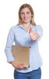 Blonde Geschäftsfrau mit der Datei, die sich Daumen zeigt Stockbild