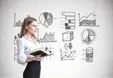 Blonde Geschäftsfrau mit einem Notizbuch, Daten Lizenzfreies Stockfoto