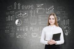Blonde Geschäftsfrau mit einem Notizbuch nahe einer Tafel mit einem sta Lizenzfreies Stockfoto