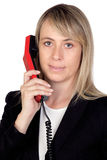 Blonde Geschäftsfrau mit einem roten Telefon Lizenzfreie Stockfotografie