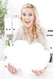 Blonde Geschäftsfrau mit einer leeren Anzeige in seiner Hand Lizenzfreies Stockfoto