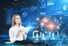 Blonde Geschäftsfrau mit einer Tablette, Hologramme Stockfotos