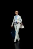Blonde Geschäftsfrau mit Koffer im weißen Anzug bereit, auf Schwarzem auszulösen Lizenzfreie Stockfotografie