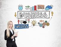 Blonde Geschäftsfrau mit Notizbuch und bunter Geschäftsskizze Lizenzfreies Stockbild