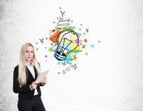 Blonde Geschäftsfrau mit Notizbuch und bunter Glühlampeskizze Lizenzfreie Stockbilder