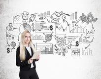 Blonde Geschäftsfrau mit Notizbuch und schwarzer Startskizze Lizenzfreies Stockbild