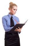 Blonde Geschäftsfrau mit schwarzem Faltblatt und roter Feder Stockfotografie
