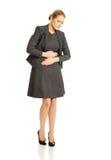 Blonde Geschäftsfrau mit starken Magenschmerzen Lizenzfreies Stockbild