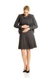 Blonde Geschäftsfrau mit starken Magenschmerzen Lizenzfreie Stockfotos