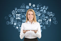 Blonde Geschäftsfrau nahe Geschäftsideenskizze auf blauer Wand Lizenzfreies Stockfoto