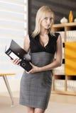 Blonde Geschäftsfrau nimmt Klassifikator Stockfoto