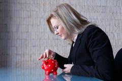 Blonde Geschäftsfrau setzte Münzen in Sparschwein Stockbilder