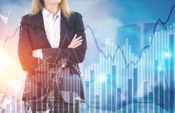 Blonde Geschäftsfrau und Diagramme in einer Stadt Lizenzfreie Stockbilder