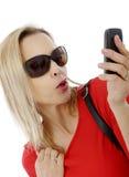 Blonde Geschäftsfrau von mittlerem Alter mit Telefon und Sonnenbrille Lizenzfreies Stockbild