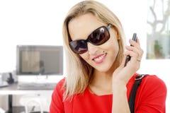 Blonde Geschäftsfrau von mittlerem Alter mit Telefon und Sonnenbrille Stockbild