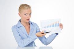 Blonde Geschäftsfrau, welche die Kamera hält ein Diagramm betrachtet Lizenzfreies Stockfoto