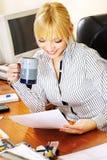Blonde Geschäftsfrau, welche die Papiere im Büro überprüft Stockfoto