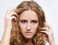 Blonde girl. Portrait of blue-eyed curly blonde girl on gray stock photos