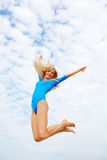 Blonde girl. Outdoor portrait of young beautiful happy blonde woman gymnast jumping in blue sky Royalty Free Stock Image