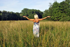 Blonde girl alone in field. From the back. Royalty Free Stock Image