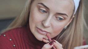 Blonde girl apply lipstick with cosmetic pencil on the lips stock video footage