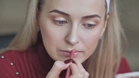 Blonde girl apply lipstick with cosmetic pencil on the lips stock footage