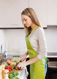 Blonde girl in apron cooking with vegetables. At domestic kitchen Royalty Free Stock Photography